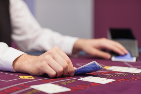 croupier: Dealer dealing cards at table of a casino