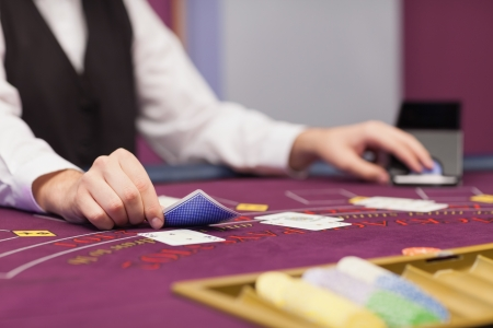 Dealer sitting at table in a casino while distributing cards photo
