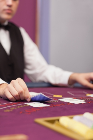 distributing: Dealer distributing cards in a casino while sitting at table