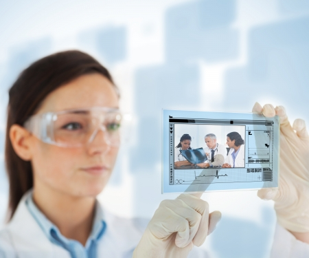 Woman pointing on picture of doctor and nurses looking at x ray on hologram interface on blue and white background photo
