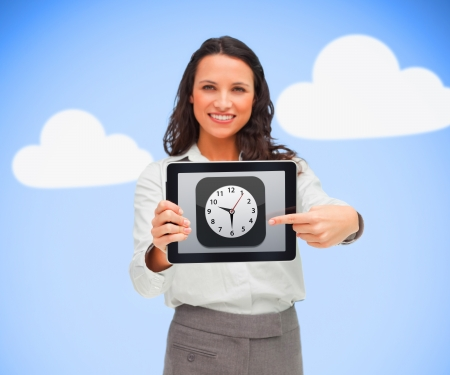 Woman standing while smiling and holding a tablet pc with clock symbol on blue cloud background photo