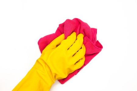 out of context: Hand wearing yellow rubber gloves cleaning with pink cloth