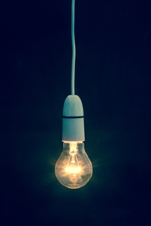 hanging on: Light bulb turned on over black background Stock Photo