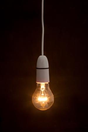 light fixture: Bright light bulb turned on over black background Stock Photo