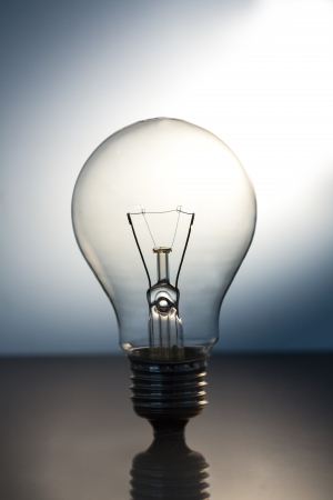 suface: Big bright light bulb standing on a reflective suface