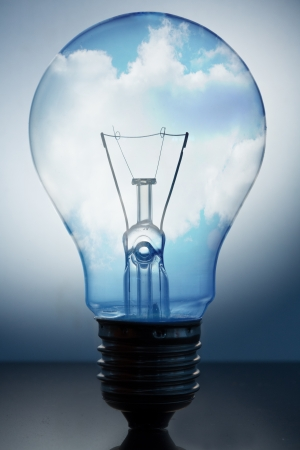 fluorescent light: Close up of big light bulb standing with bright blue sky with clouds in it