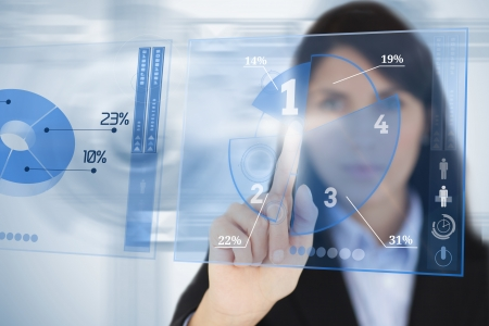 Serious businesswoman using blue pie chart futuristic interface by touching it photo