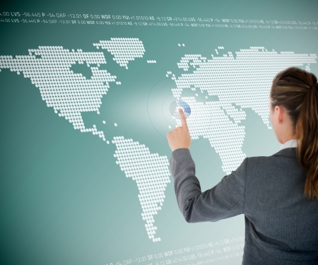 futuristic woman: Well dressed business woman using futuristic interface with map on the background Stock Photo