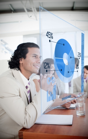 multiracial: Smiling businessman looking at blue pie chart interface in a meeting