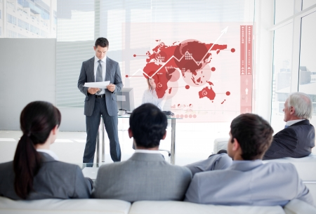 concentrate: Business people listening and looking at red map diagram interface in a meeting