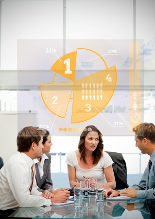 Business workers using yellow pie chart interface in a meeting photo