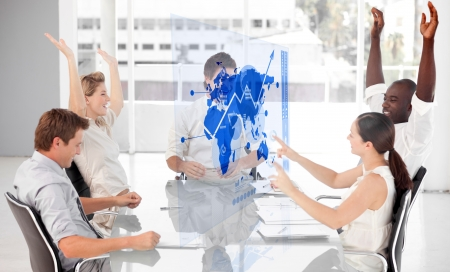 Cheerful business workers using blue map diagram interface in a meeting photo