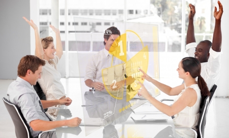 multiracial: Cheerful business workers using yellow pie chart interface in a meeting Stock Photo