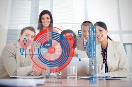 multiracial: Smiling business workers looking at colorful pie chart interface in a meeting Stock Photo
