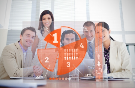 Smiling business workers looking at orange pie chart interface in a meeting photo