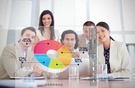 wykres kołowy: Uśmiechnięci pracownicy firmy patrząc na kolorowe interfejs wykresu kołowego w spotkaniu