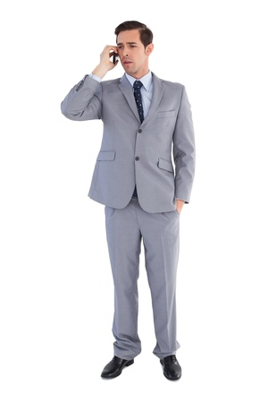 Businessman confused while being on the phone on white background  photo