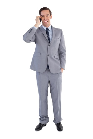 Happy businessman on the phone on white background photo