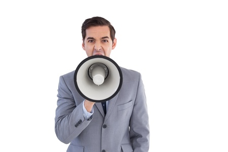 Businessman shouting into a megaphone on white background photo