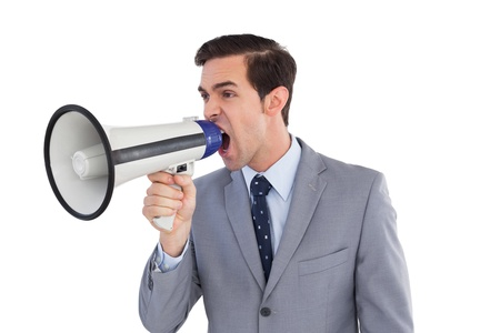 businessman using a megaphone: Businessman yelling into a megaphone on white background