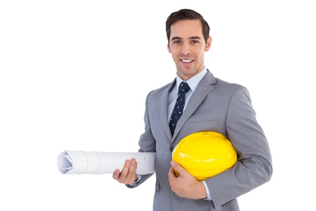 well dressed  holding: Smiling architect holding plans and hard hat on white background