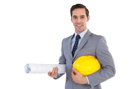 architect: Smiling architect holding plans and hard hat on white background