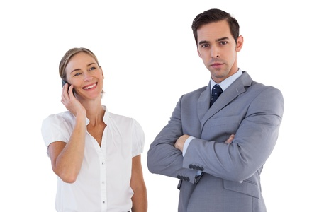 Smiling businesswoman on the phone next to her colleague on white background photo