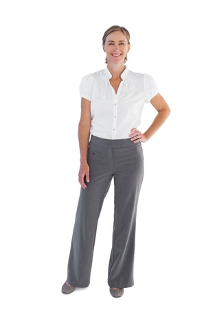 fair woman: Smiling businesswoman standing with her hand on her hip on white background