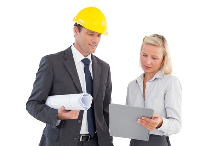 Architects with hard and plans looking at clipboard on white background photo