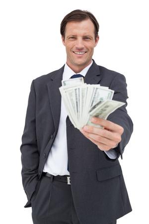 Smiling businessman holding cash on white background photo