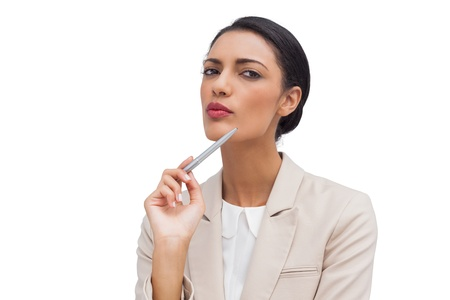 Thoughtful young businesswoman holding a pen on white background Stock Photo - 20499495
