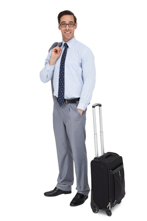 Smiling businessman standing next to his luggage on white background photo