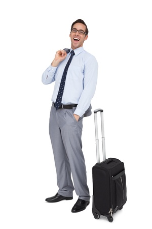 Laughing businessman standing next to his suitcase on white background photo