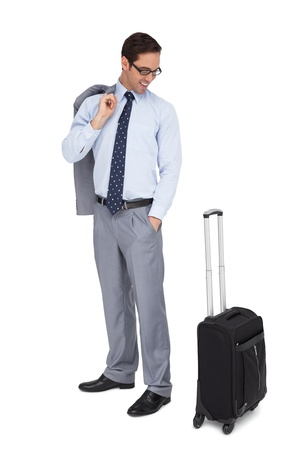 Smiling businessman looking at his suitcase on white background photo
