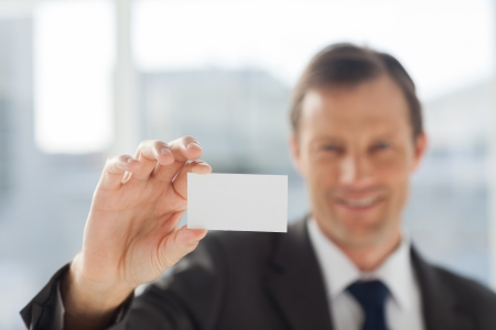 Smiling businessman showing business card in his office photo