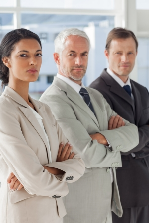 Three serious business people standing together with their arms crossed photo