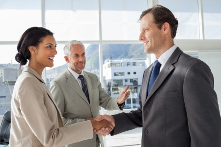 businessmen handshake: Businessman introducing a colleague to another businessman