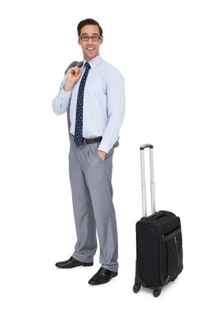 Happy businessman waiting next to his luggage on white background photo