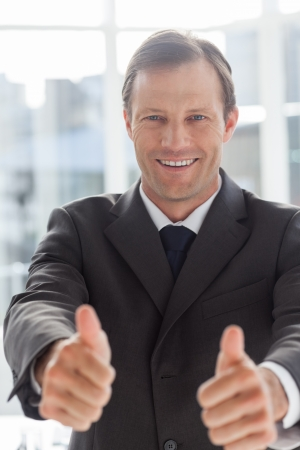 Smiling confident businessman giving thumbs up in his office photo