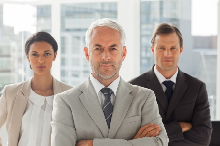 Serious businessman standing with colleagues behind with arms folded photo