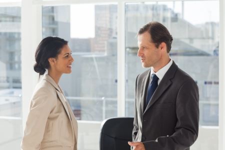 women talking: Smiling colleagues speaking together in an office Stock Photo