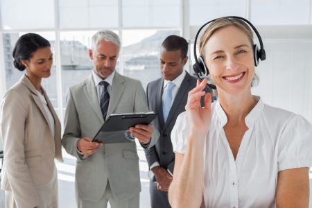 Smiling woman standing with a headset with colleagues working behind photo