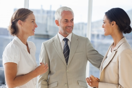 likeable: Likeable businessman speaking with female colleagues during working hours