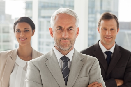 Businessman standing with colleagues behind with arms crossed Stock Photo