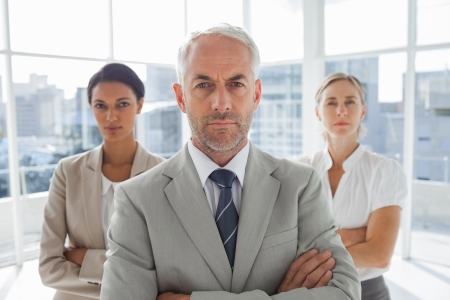 Serious businessman standing in front of colleagues with arms crossed photo
