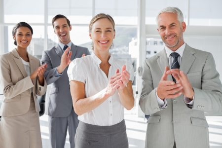 and acclaim: Smiling business people applauding together in the meeting room Stock Photo