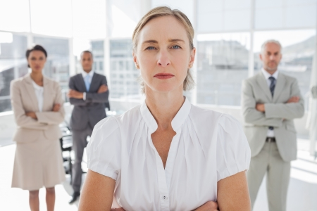Serious businesswoman standing with arms folded with colleagues behind photo
