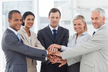 team building: Group of business people piling up their hands together in the workplace Stock Photo