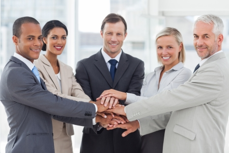 Group of smiling business people piling up their hands together in the workplace
