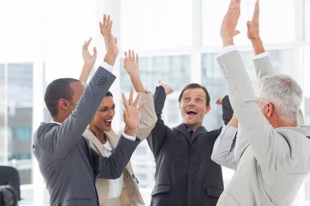 Groep van lachende mensen uit het bedrijfsleven die hun handen op de werkplek